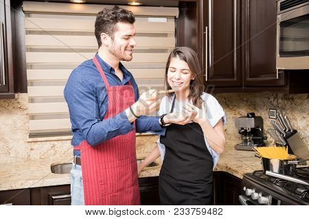 Beautiful Woman Tasting Food Prepared By Her Boyfriend In Kitchen At Home