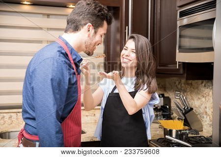 Pretty Woman Feeding Food To Her Boyfriend For Tasting In Kitchen At Home