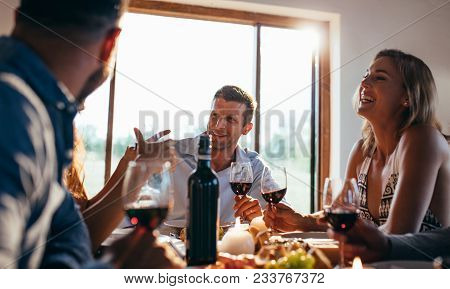 Friends Sitting At A Table And Talking During A Dinner Party. Men And Women Dining Together At Home.