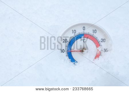 Thermometer with celsius scale placed in a fresh snow showing sub-zero temperature minus 30 degree - extreme cold winter weather concept