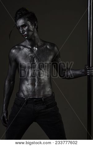 Guy Puts Hand On Metallic Pole. Man With Nude Torso Covered With Shimmering Silver Paint, Dark Backg