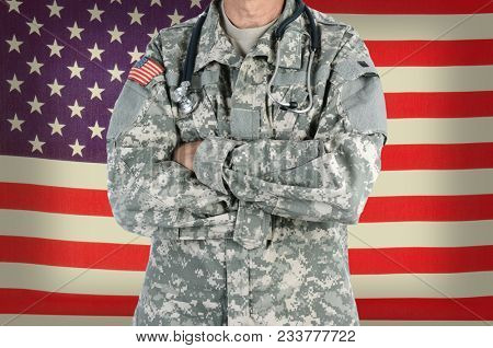 Closeup of a military doctor with a stethoscope around his neck in front of American Flag. The man is wearing camouflage fatigues also called ACU and has his arms crossed.