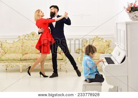 Boy Adorable Try To Play Piano Musical Instrument, While Parents Dancing. Child Sit Next To Piano, P