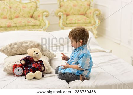 Boy With Happy Face Puts Favourite Toy On Bed, Time To Sleep. Kid Put Plush Bear Near Pillows And Al