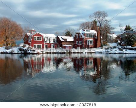 Beautiful snowcovered houses reflected in the pond , winter