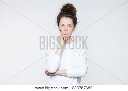 Angry Annoyed Young Housewife Keeping Arms Crossed And Staring At Camera With Sceptic, Distrustful L
