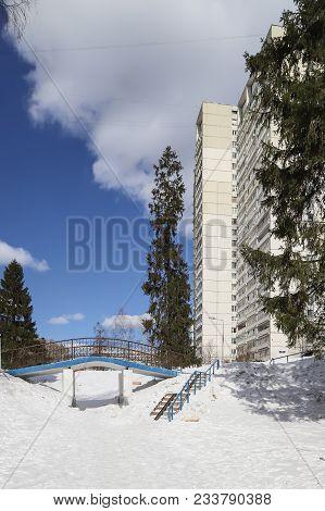 Blue Design Bridge In A Winter City Near A High-rise Building