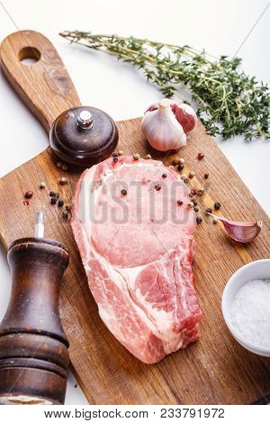 Raw Pork Natural Cutlet With Beam Thyme, Garlic, Salt, Pepper, Salt And Pepper Shakers On The Wooden