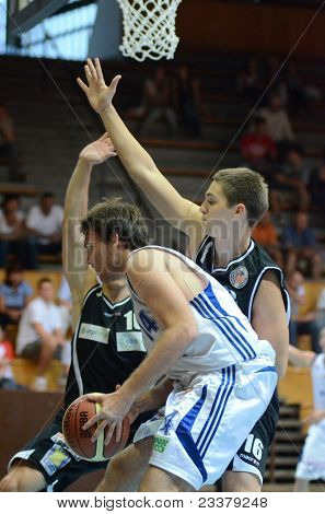 KAPOSVAR, HUNGARY - SEPTEMBER 8: Bence Biro (in white) in action at a friendly basketball game between Kaposvar (white) and Pecsi VSK (black) September 8, 2011 in Kaposvar, Hungary.