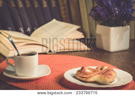 A Cup Of Coffee And A Plate With Baking. Books On The Shelf, Books On The Table. A Pot Of Flowers On
