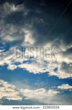 A Blue Sky Filled With Dark And Light Clouds, Hiding The Sun.