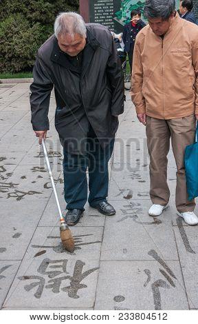 Beijing, China - April 26, 2010: Tuanjiehu Park. Older Man Draws Mandarin Characters In Calligraphy