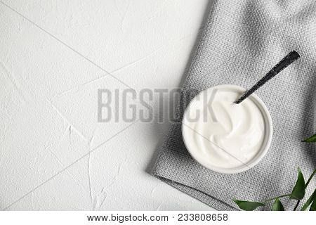 Bowl and spoon with yummy yogurt on table poster