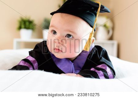 Little Baby Girl In Graduation Cap And Gown