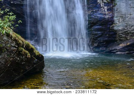 A beautiful cascading waterfall splashing into an emerald pool with large wet rocks