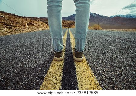 Men`s Feet Standing On Asphalt Desert Road With Yellow Marking Lines. Man Wearing Sneakers And Jeans