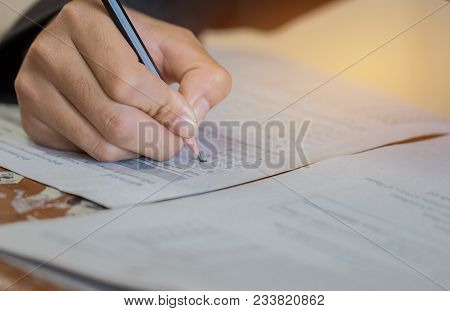 Front View Asian Students, Undergraduate Holding Pencil Writing On Multiple-choice Quizzespaper Answ