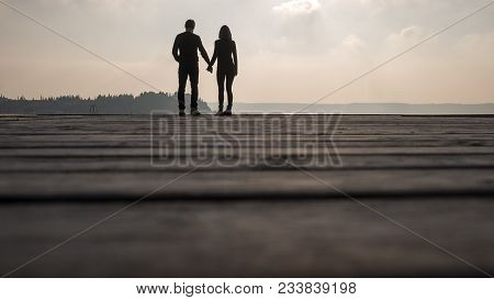 Silhouette Of Romantic Couple Holding Their Hands While Standing On Wooden Pier On The Seashore.