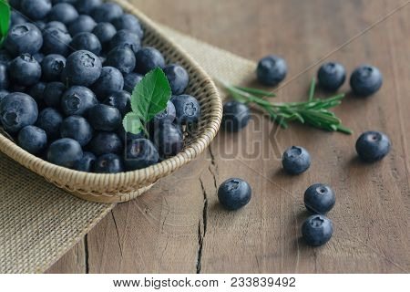 Fresh Wild Blueberries In Wood Basket On Sack. Wild Blueberry Put On Wooden Table With Copy Space Fo