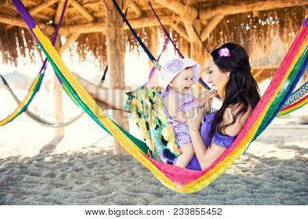 Happy Stylish Family With Cute Daughter Relaxing In Hammock On Summer Vacation In Evening Sun Light