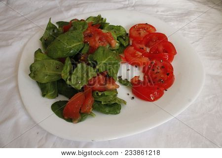 Appetizing  Salad From Raw Ripe Juicy Vegetables Under Spicy And Sauce On White Plate