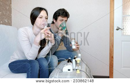 Use Nebulizer And Inhaler For The Treatment. Man And Woman Inhaling Through Inhaler Mask. Front View