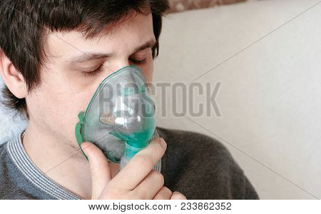Use Nebulizer And Inhaler For The Treatment. Closeup Young Man's Face With Cloused Eyes Inhaling Thr