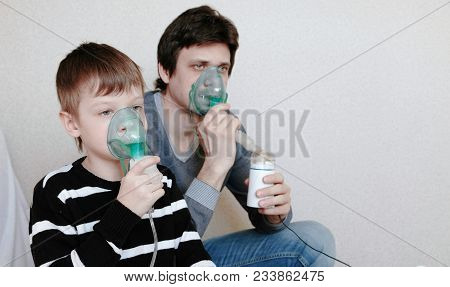 Use Nebulizer And Inhaler For The Treatment. Man And Boy Inhaling Through Inhaler Mask. Side View