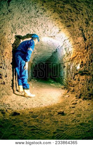 Workerman With Helmet And Protective Suit Using Glowes And Head Lamp. Man Do Job In Old Mine Ventila