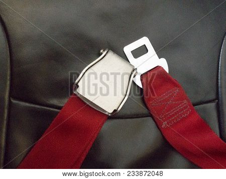 Red Seat Belt In Airplane To Save Life While Flying In Sky. Safety And Travel Concept.
