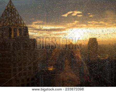 Drop Of Water On Widow Glass With Light Sunset In City And Building View. Rainy Season Feeling Alone