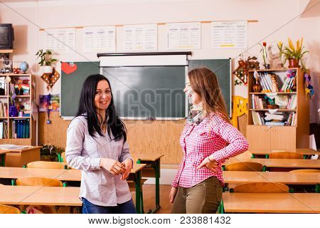 Two Young Women Teacher Standing In The Middle Of The Classroom
