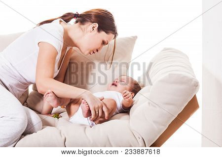 A Young Mother Consoled The Baby On The Sofa