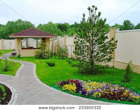 Beautiful Landscape Design In A Private Yard. Colorful Flowers, Green Grass And Trees. Cosy Barbeque
