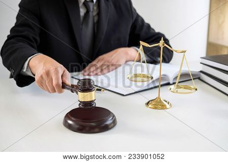 Close Up Of Male Lawyer Or Judge Hand's Striking The Gavel On Sounding Block, Working With Law Books