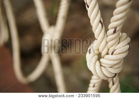 White Rope Tied In A Knot For Adventure. Close-up Of Rope Knot Line Tied Together With Bridge Backgr