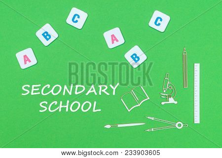 From Above School Supplies Wooden Minitures And Abc Letters On Green Background With Text Secondary