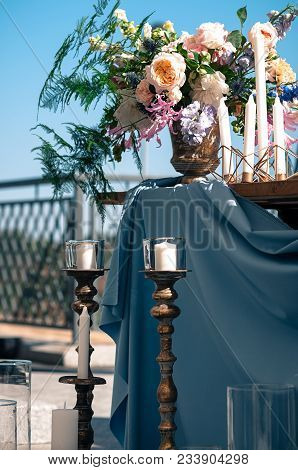 Wedding Or Other Catered Event Setting, Flowers, Candles, Blue Napkins And Tablecloth, Wooden Tables