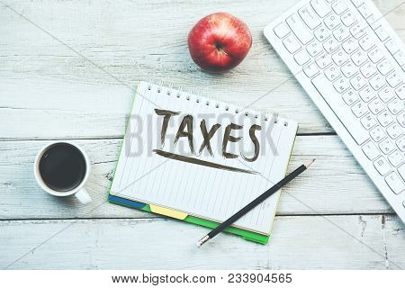 Taxes Text On Notebook With Coffee,apple And Keyboard On Table