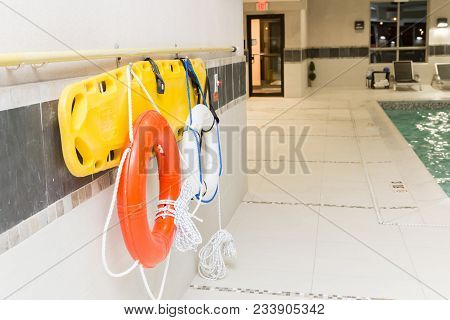 Horizontal Image Of A Life Buoy And Rescue Ring Hanging On The Wall By Indoor Swimming Pool.