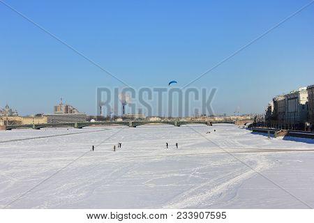 People Walking On Ice Frozen River In St. Petersburg, Russia. Winter Scene Cityscape View Of Neva Ri