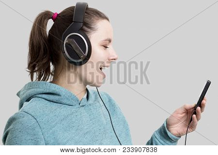 Young Attractive Brunette Girl In Headphones With Player. Beautiful Woman Listening To Music With He