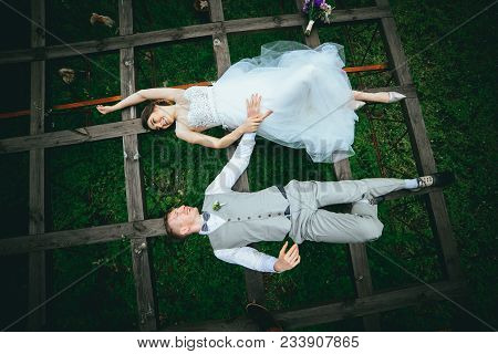 Beautiful Fabulous Happy Bride And Stylish Groom Lying Down On The Grass On The Background Of The Su