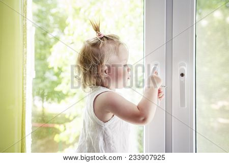 Small Child Is Standing On Windowsill And Opens Window. Locks On Windows Prevent Children From Falli