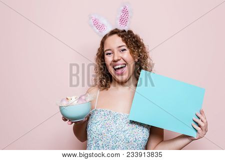 Beautiful Woman Hold Easter Decorations With Bunny Ears On Pink Color Background With Copy Space.