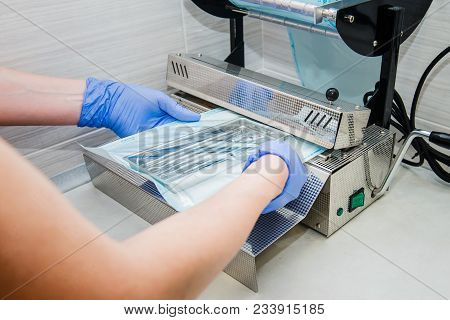 Close Up Dentist's Assistant Hands In Gloves Packing Dental Instrument Set For Autoclaving In A Plas