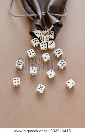 Set Of Gaming Dice Rolled Out Of Leather Bag On Brown Background. Concept With Copy Space For Games,