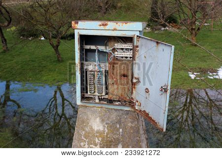 Rusted Metal Electrical Junction Box With Open Door Mounted On Concrete Pole And Surrounded With Wat