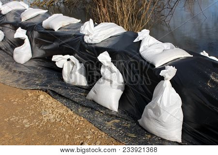 Sandbags Flood Protection On Sand And Rock Foundation Holding Back Water From Flooded River Covered