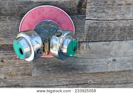 Twin Fire Hose Fitting Splitter, Also Know As Siamese Connection Sticking Out Of Wooden Wall